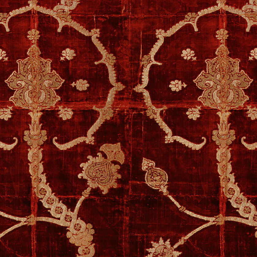 An ornate gold-leafed design against a dark wooden background