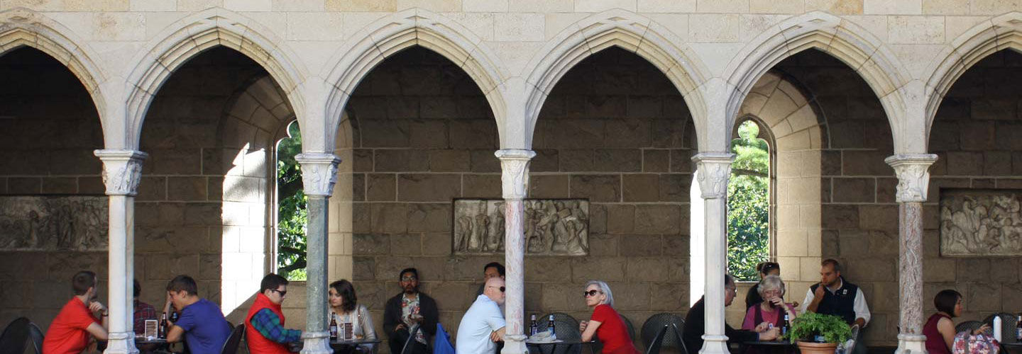 A group of people dine in a cafe situated in a stone medieval cloister