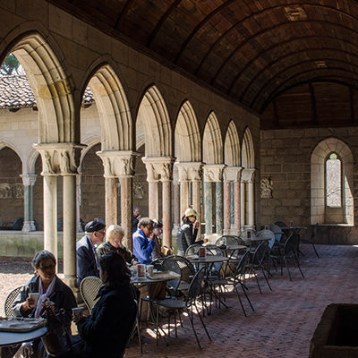 Café tables and chairs in a stone arcade overlooking a garden