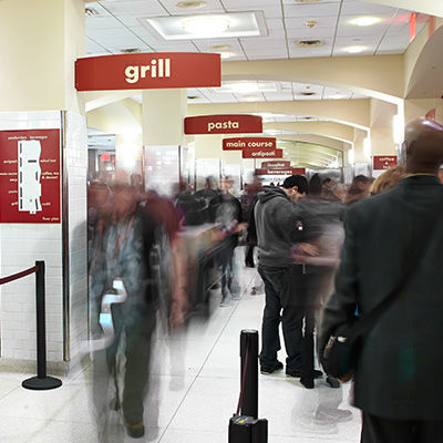 A busy cafeteria with many people selecting food; signs indicate individual food stations