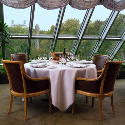 An elegant dining room with a floor-to-ceiling skylight; a table for four is draped with a white tablecloth and set with a casual-elegant service
