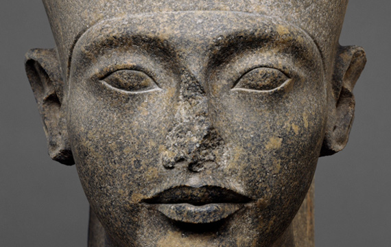 Detail view of an ancient Egyptian sculpture of the head of the god Amun