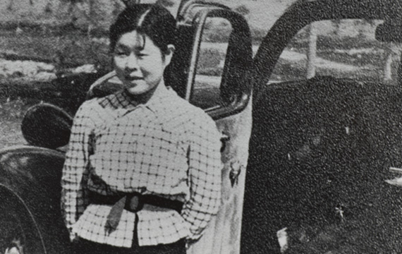 Black and white photograph of a Japanese woman standing by a car