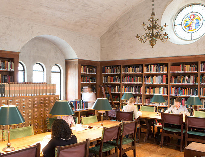 A small library lined with dark wood book shelves and tables with lamps and green upholstered chairs, arched windows, and a stained glass rosette set high in the far wall