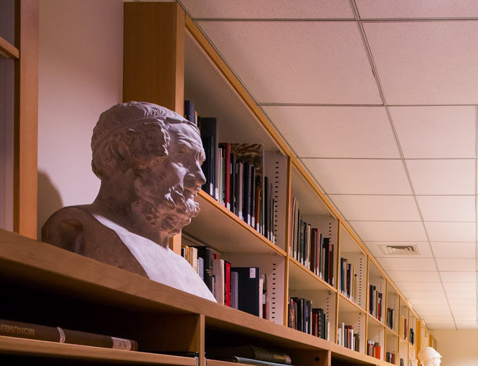 A library with shelves of books and a bust made in the tradition of Greek and Roman sculpture