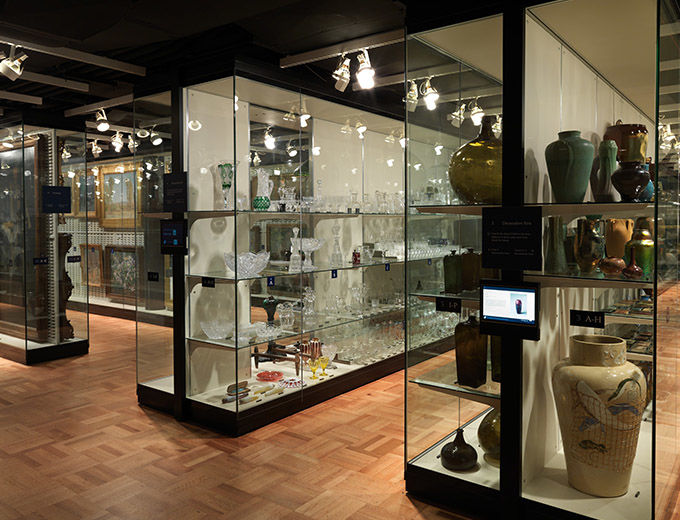 A gallery filled with glass-fronted shelving filled with art objects from the American Wing; touch screens are mounted along side all the cases
