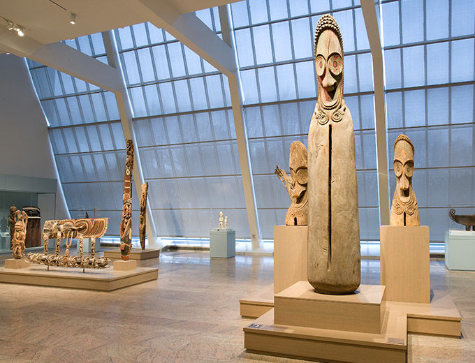 A large open gallery with a wall of windows; in the foreground is one very tall and two smaller wooden sculptures from Oceania