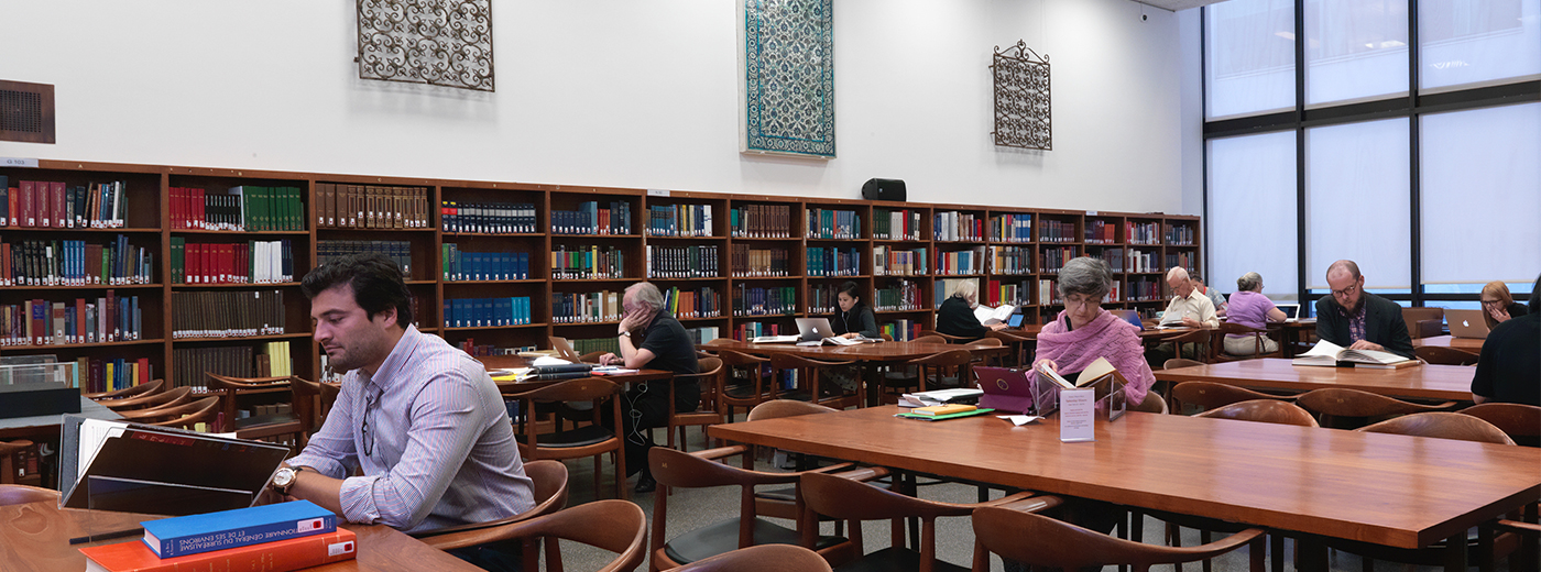 A large, modern, brightly lit room in a library lined with shelves of books; in the center are long rectangular wooden tables with chairs, researchers and students with laptops and books are working at the tables