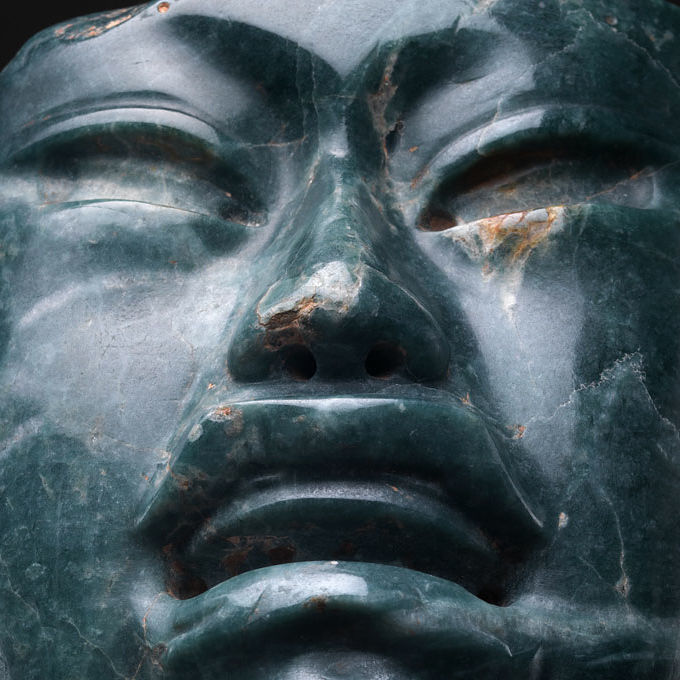 A close-up of a dark-green stone sculpture's face