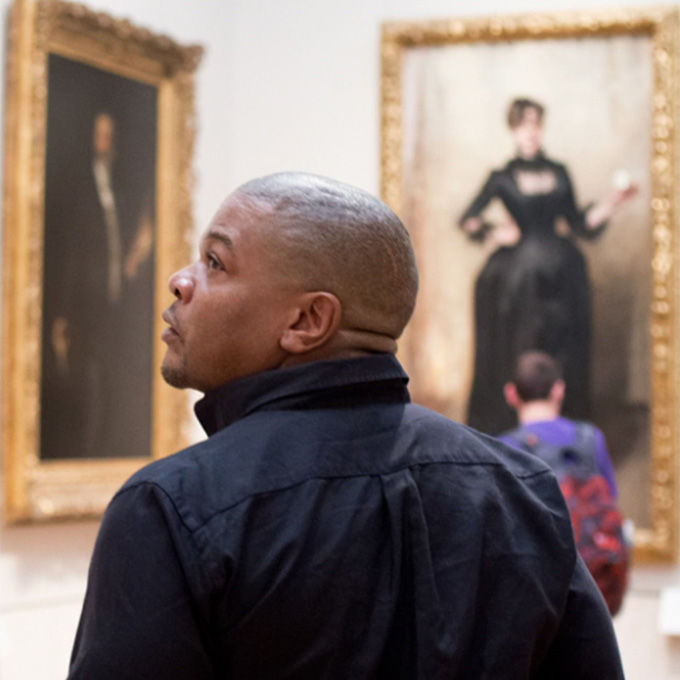 Man in American paintings gallery turning to look at a painting on his left
