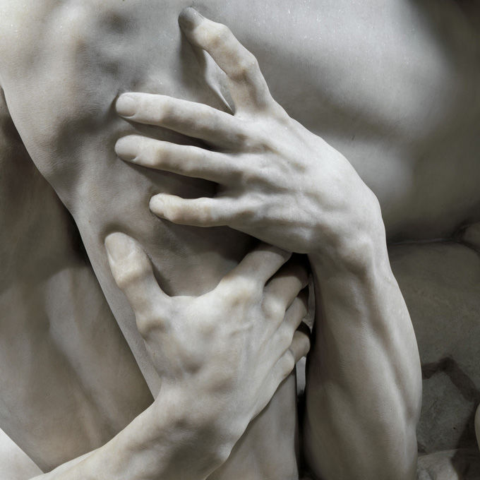 Detail view of a marble sculpture in which we see a hand grasping another piece of flesh