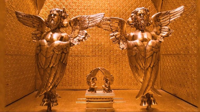 A golden model room with two gold statues of ancient angels and an ornate cabinet between them.
