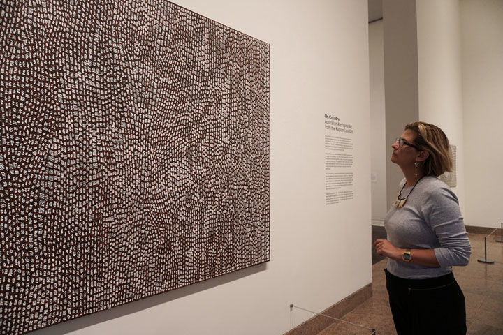 Curator conversation exploring contemporary aboriginal art with associate curator maia nuku observes a painting on view in an exhibition gallery solutioingenieria Choice Image
