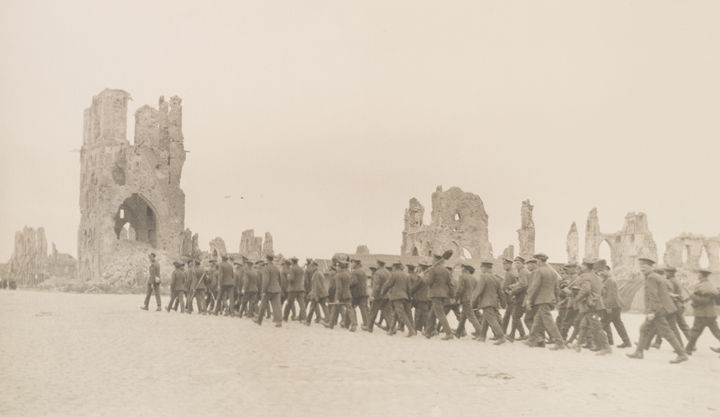 Photo by Margaret Hall showing a group of soldiers marching toward the ruins of a Belgian cathedral