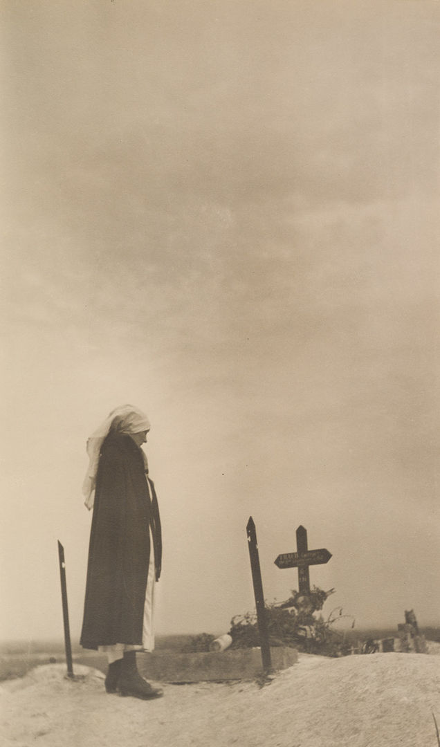 Photo by Margaret Hall of a woman standing over an unmarked grave in 'No-Man's-Land'