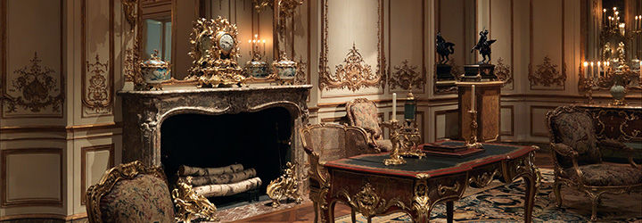 A warmly lit interior featuring a French period room filled with furniture and a large fireplace.
