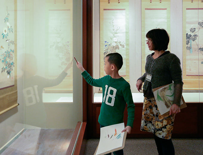 A child and mother view a display in the Asian art galleries