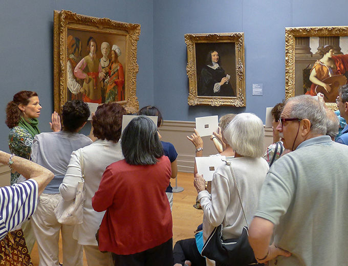 Visitors in the European paintings gallery listening to a museum educator during a gallery talk