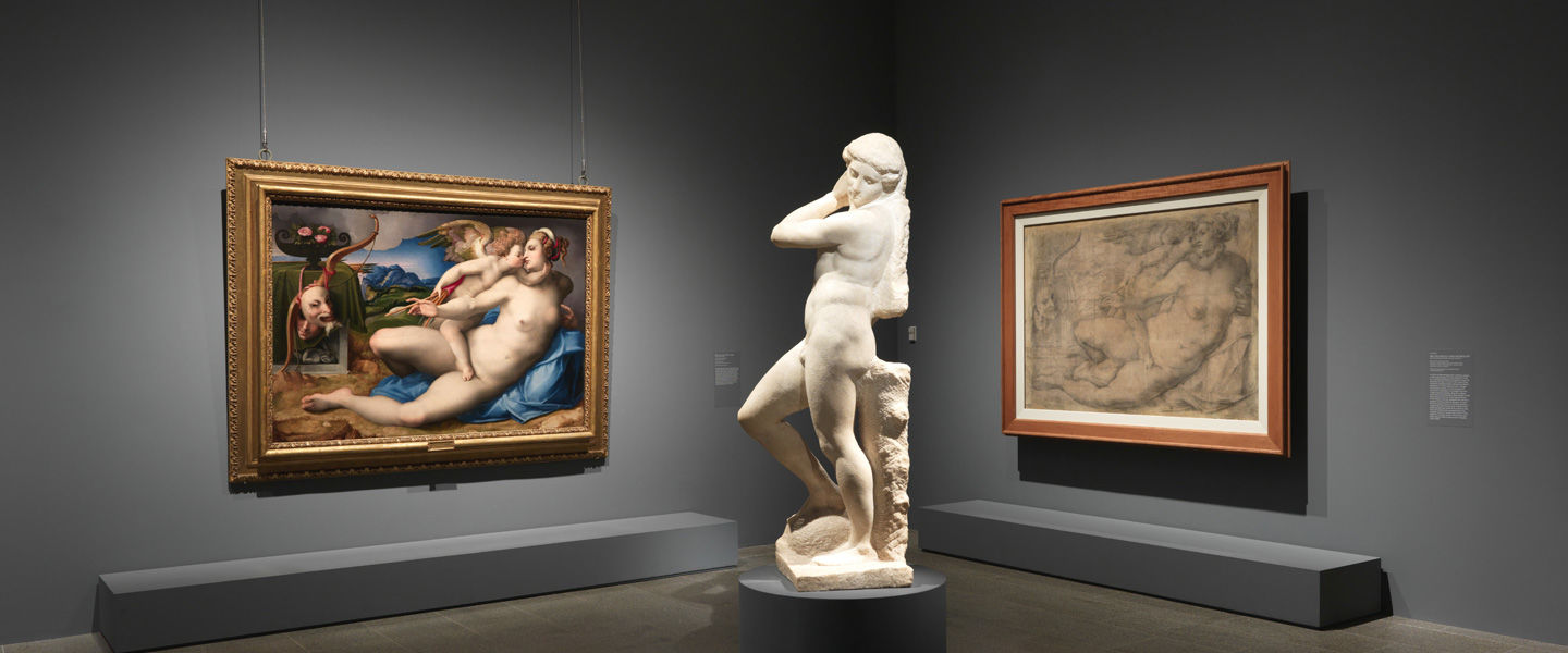 Installation view of the exhibition 'Michelangelo: Divine Draftsman and Designer' featuring a marble sculpture and a full-scale cartoon by Michelangelo