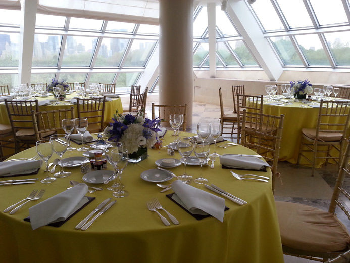 A Bright Sunlit Interior Terrace Set With Round Dining Tables Draped In Yellow Table