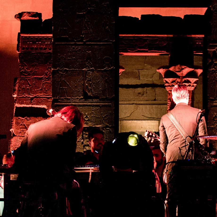 A large gallery with an ancient Egyptian sandstone temple at night with dramatic lighting; in front of the temple, musicians with their backs to the camera are playing to a large crowd