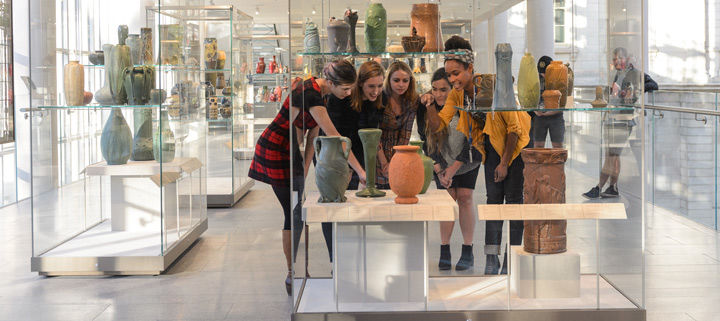 A group of young women gathered around ancient pottery
