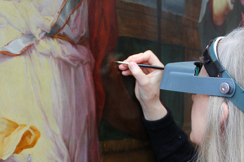 A conservator analyzes a painting up close