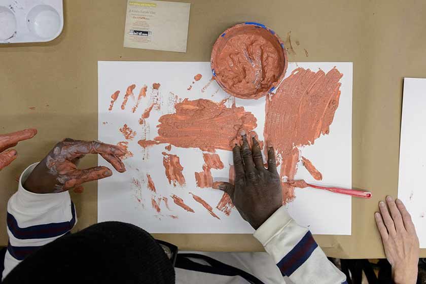A visitor who is blind paints a picture with his hands