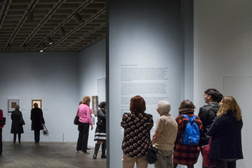 A group of museum-goers view art in a gallery in The Met Breuer