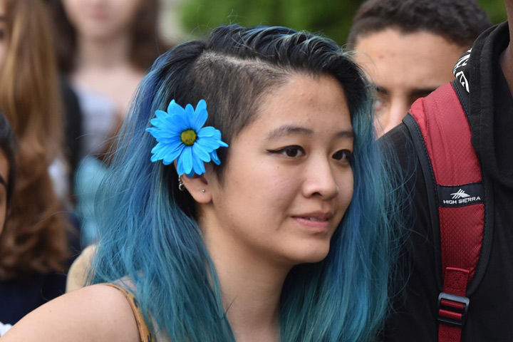 A teen with blue hair and a blue flower in her hair