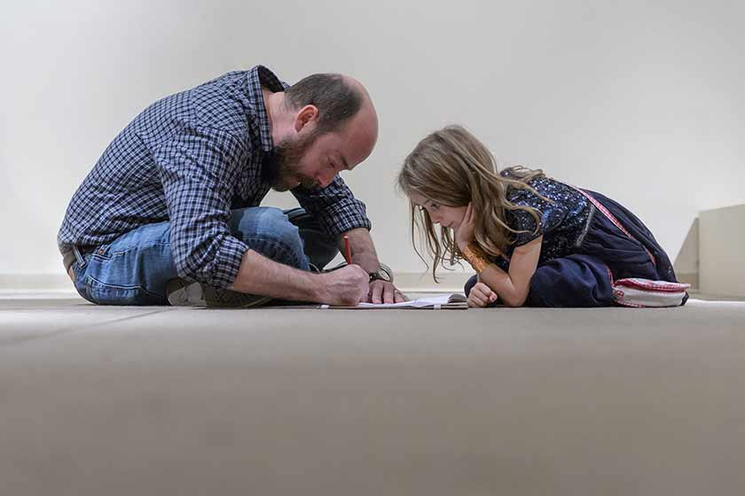 A father and daughter sketch in the galleries
