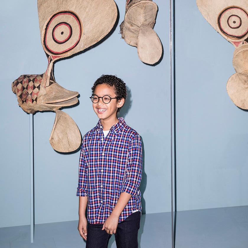 A young boy poses in front of a vitrine of Oceanic art