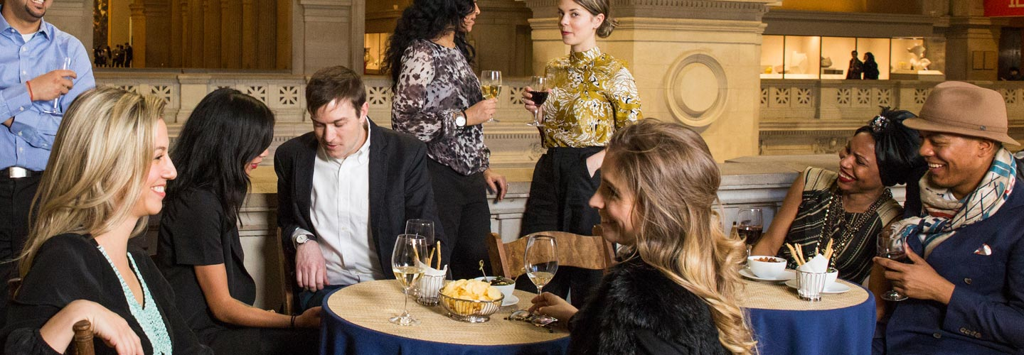 A group of people enjoy conversation, food, and drinks surrounded by the grand architecture of The Met's Great Hall