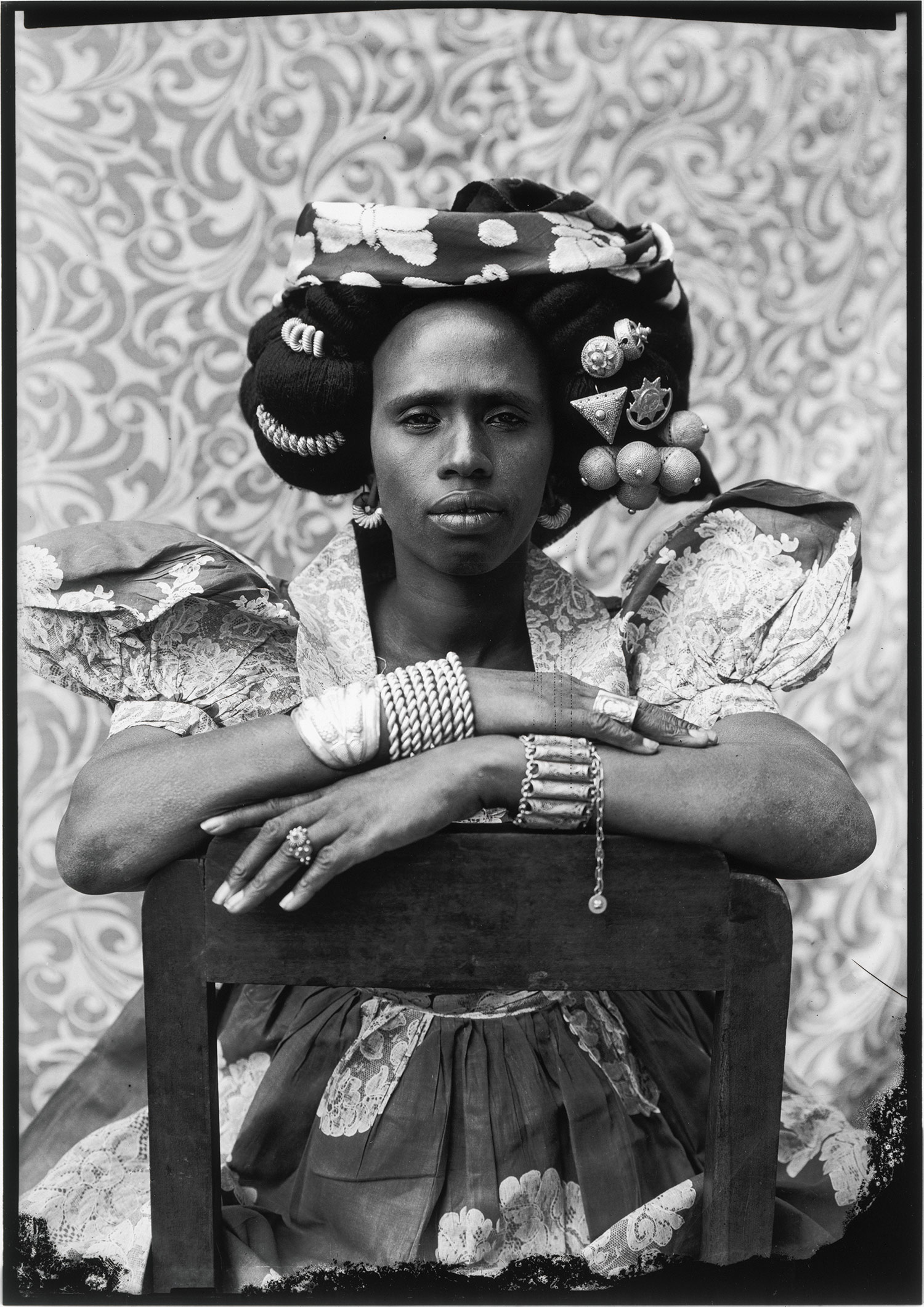 Black woman in front of printed fabric, sitting on chair