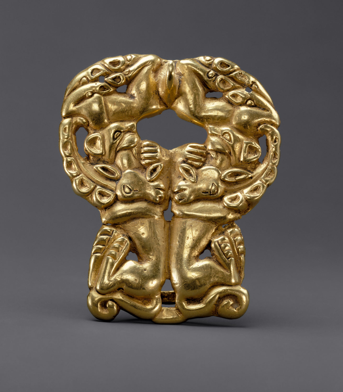 Belt buckle with paired felines attacking ibexes