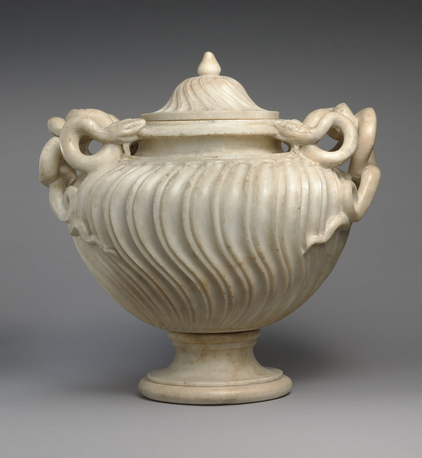 Strigilated vase with snake handles and lid