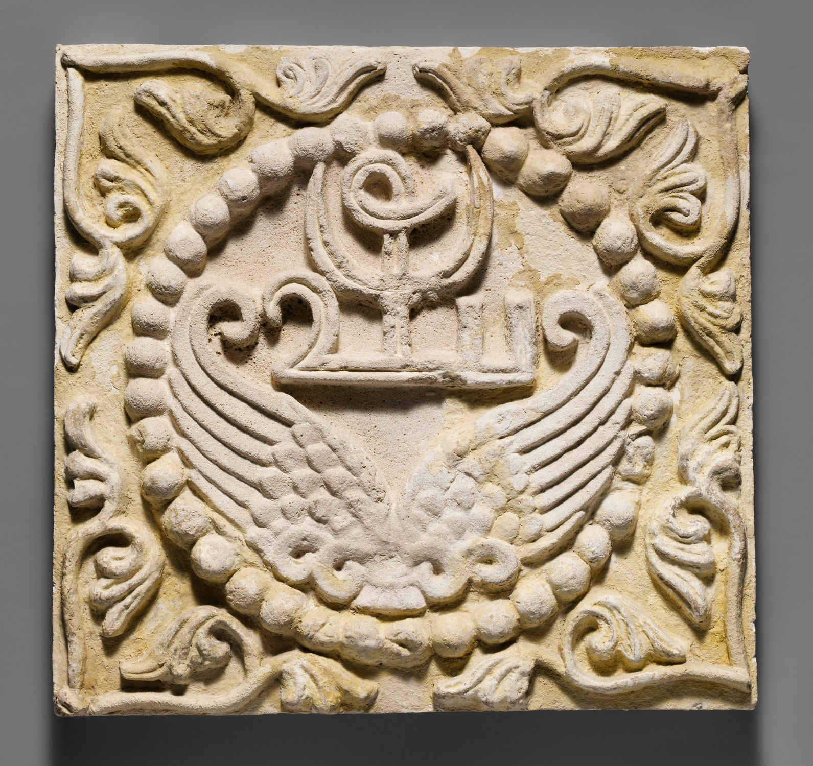 Wall panel with wings and a Pahlavi device encircled by pearls