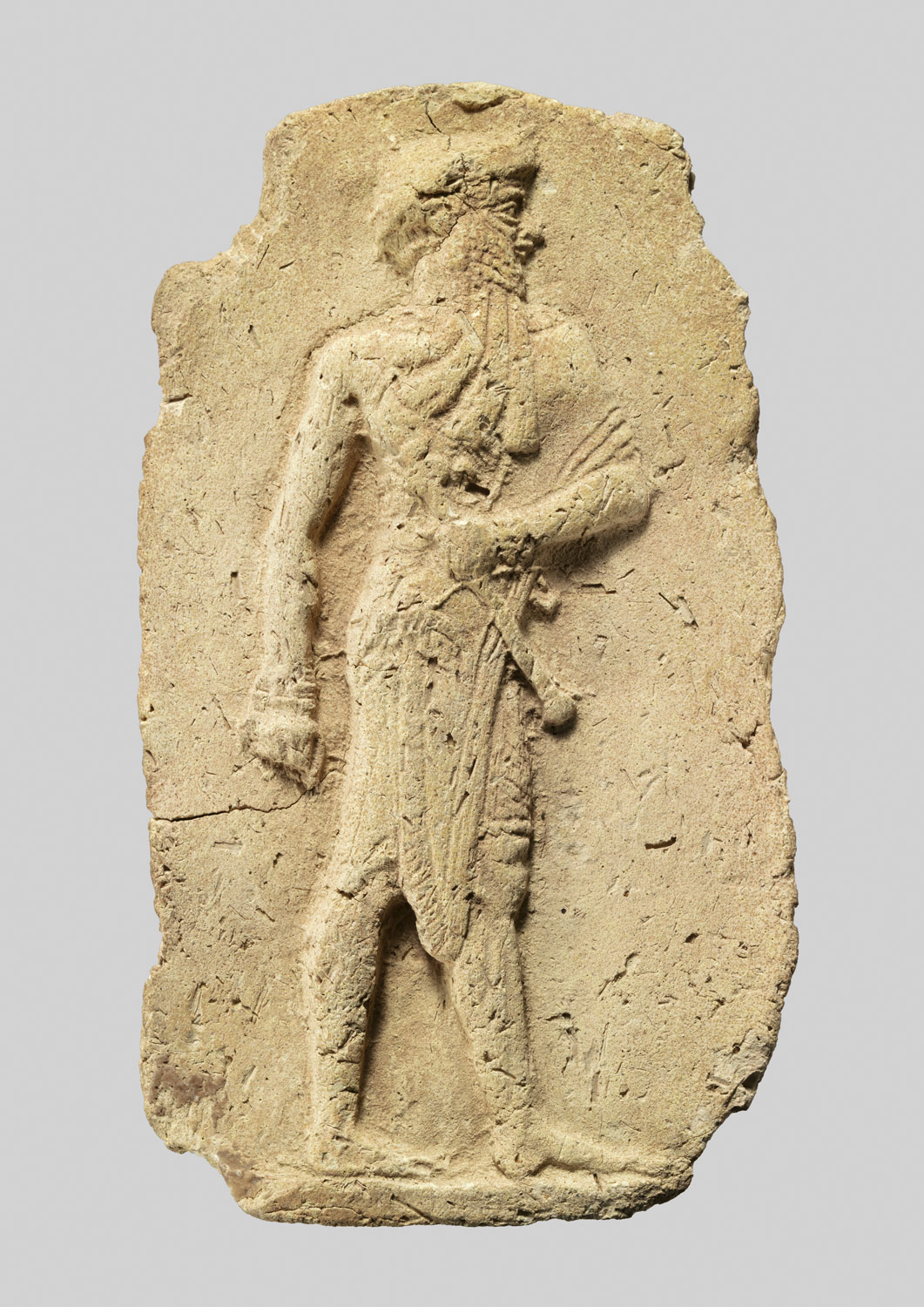 Molded plaque: king or a god carrying a mace