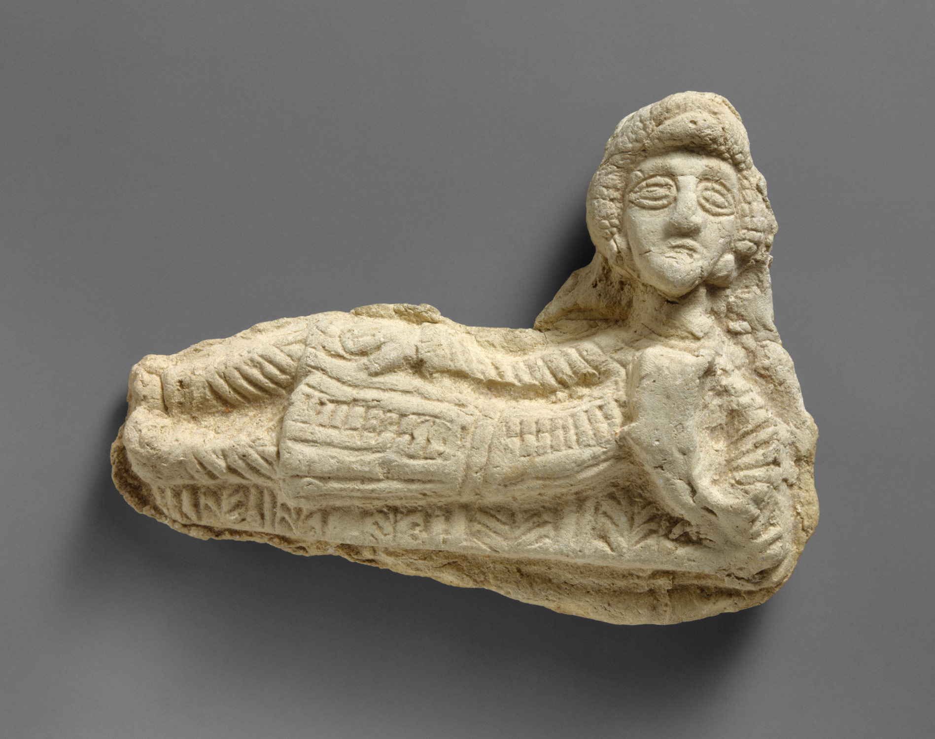 Plaque in the form of a reclining man